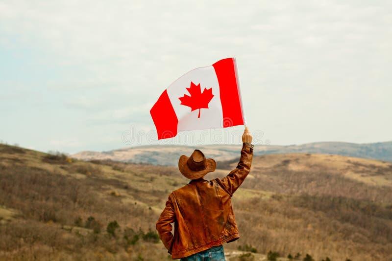 Mężczyzna w kowbojskim kapeluszu bierze kanadyjczyk flagę zdjęcia stock