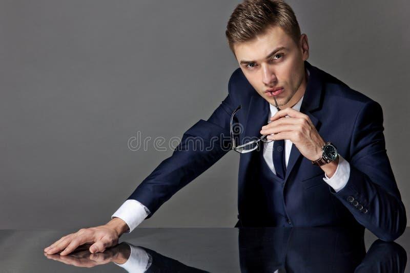 Mężczyzna w krawacie i kurtce siedzi przy stołem zdjęcie stock