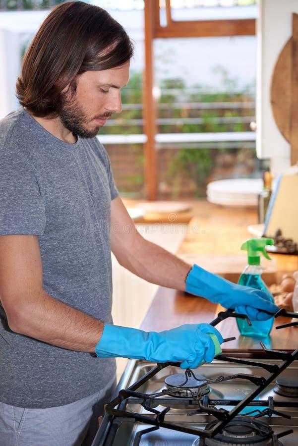Mężczyzna w kuchennej cleaning kuchence obraz stock