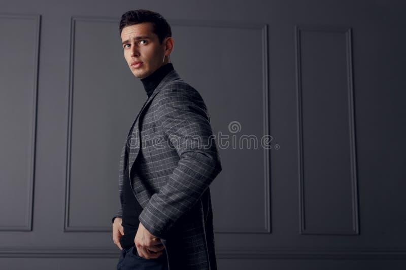 Mężczyzna w kurtce szarości turtleneck i, stoi w profilu z rękami w jego kieszeniach i patrzeje ufny obrazy stock