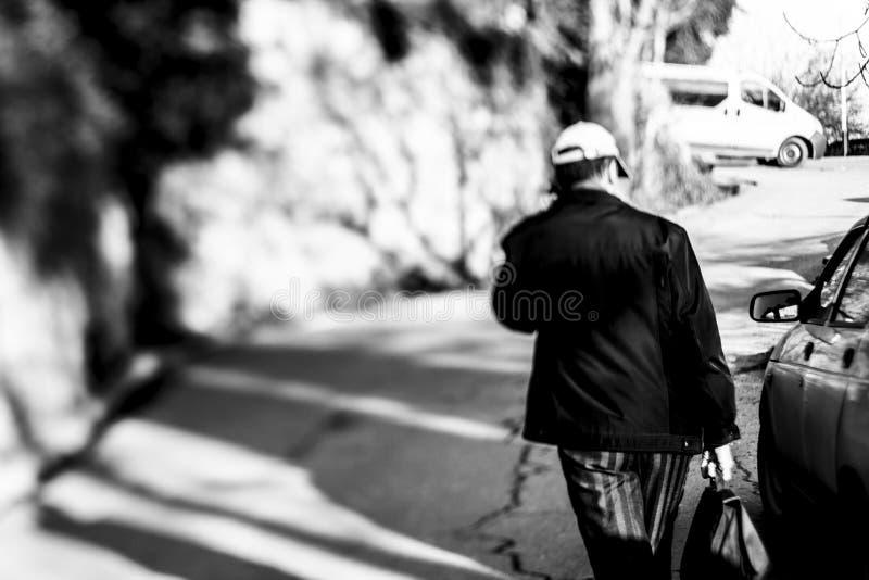 Mężczyzna w lampasów spodniach z torbą iść w górę ulicy fotografia stock