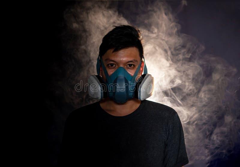 Mężczyzna w masce gazowej dymi, czarny tło zdjęcie stock