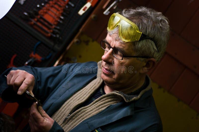Mężczyzna w metalu warsztacie z pomiarowym narzędziem fotografia royalty free