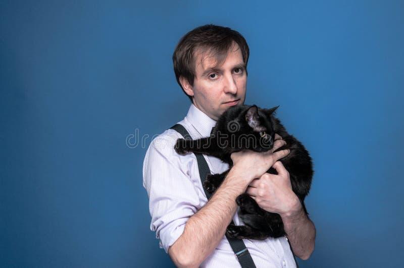 Mężczyzna w mieniu i przytulenie czarnym śmiesznym kocie koszula i suspender zdjęcia stock