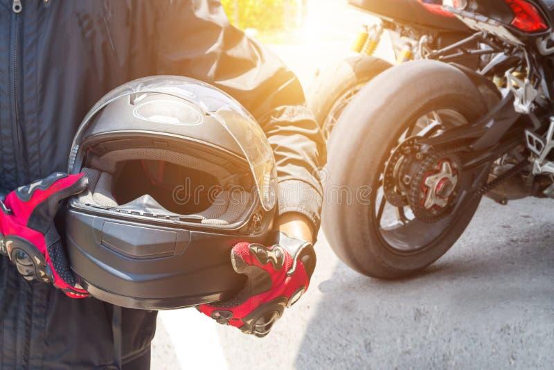 Mężczyzna w motocyklu z hełmem i rękawiczkami jest znacząco ochronnym odzieżą dla motorcycling przepustnicy kontroli z słońca świ zdjęcia stock