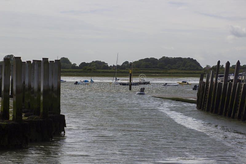 Mężczyzna w nadmuchiwanym dinghy wiosłuje przeciw sztywnemu popiółowi w kierunku slipway w Bosham schronieniu w Zachodnim Sussex obraz royalty free