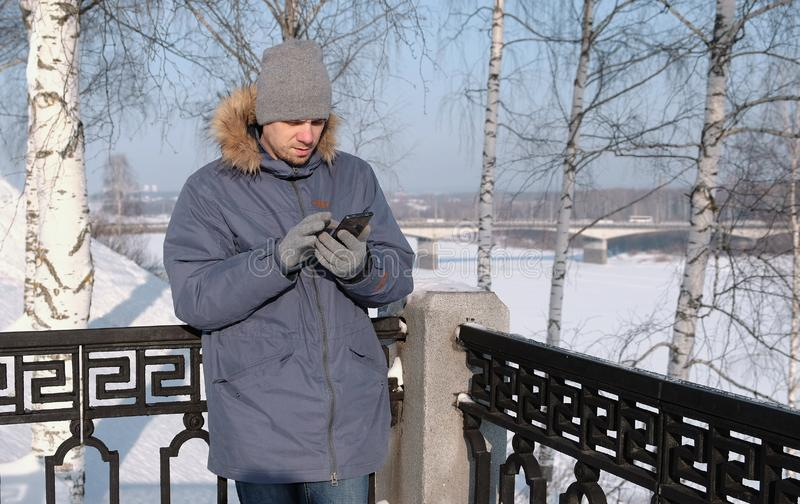Mężczyzna w niebieskiej marynarce z futerkowym kapiszonem wyciera telefonu ekran z jego ręką w rękawiczkach w zima parku obrazy stock