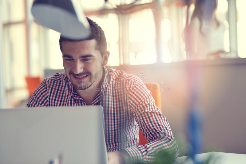 Mężczyzna w nowożytnym biurowym uruchomieniu pracuje na laptopie obraz royalty free