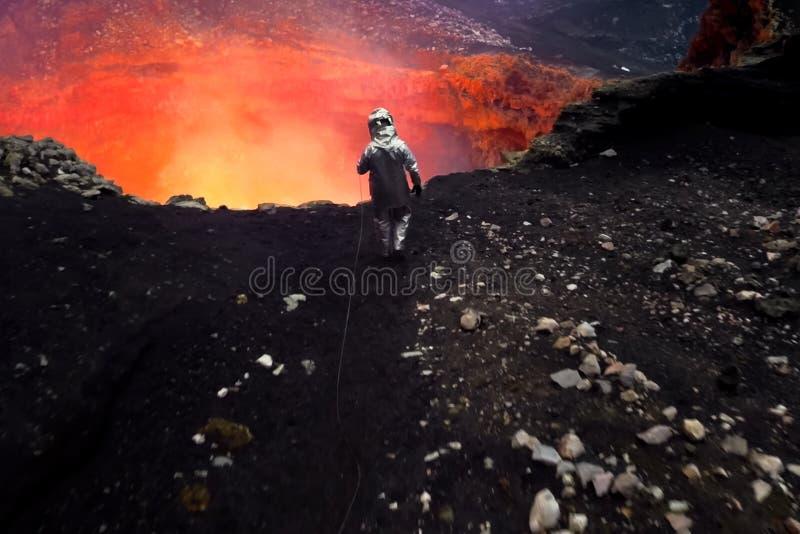 Mężczyzna w ochronnym kostiumu blisko usta wulkan Dochodzenie wulkan obrazy stock