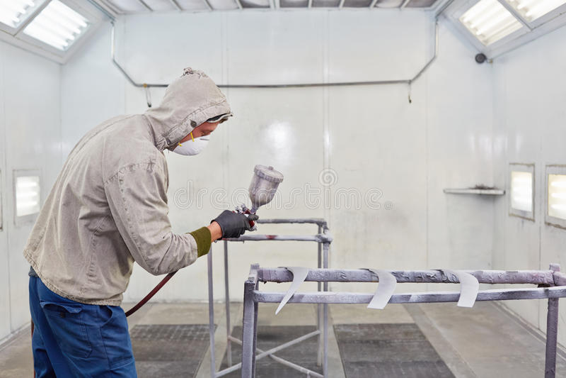 Mężczyzna w ochronnym odziewa pracy w opryskiwania budka fotografia stock