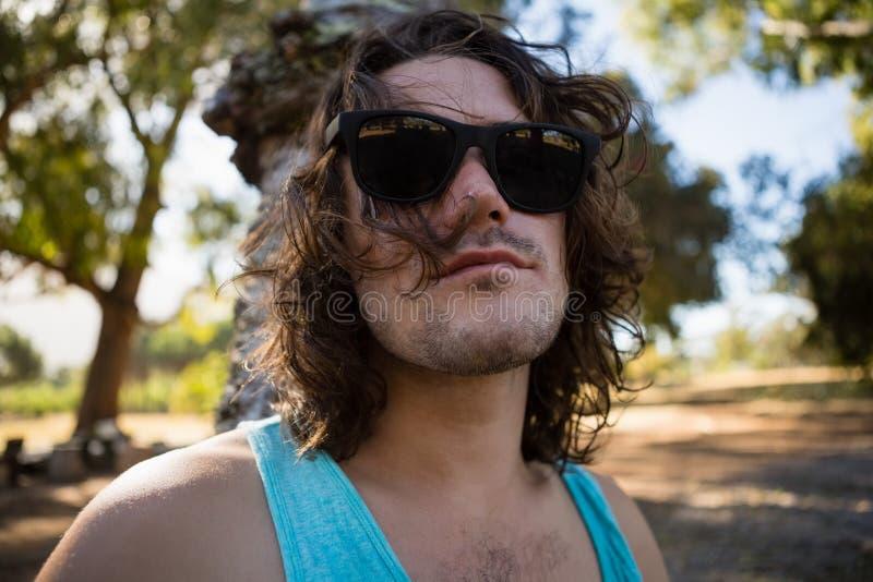 Mężczyzna w okularach przeciwsłonecznych przy parkiem zdjęcie royalty free