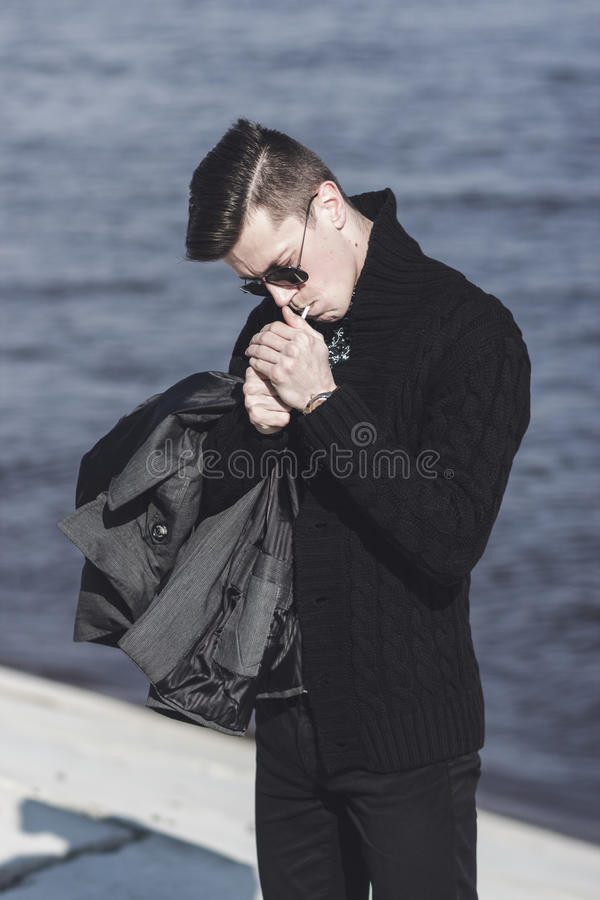 Mężczyzna w okularach przeciwsłonecznych zaświeca papieros obrazy royalty free