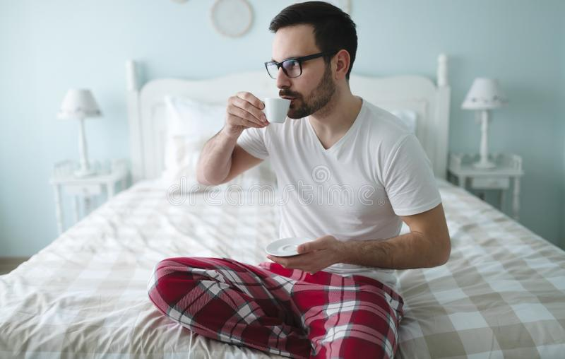 Mężczyzna w piżamach cieszy się ranek kawę obraz royalty free