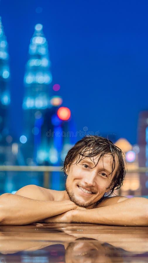Mężczyzna w plenerowym basenie z miasto widokiem w niebieskie niebo PIONOWO formacie dla Instagram mobilnej opowieści lub opowieś fotografia royalty free