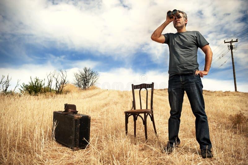 Mężczyzna w polu z lornetkami zdjęcie royalty free
