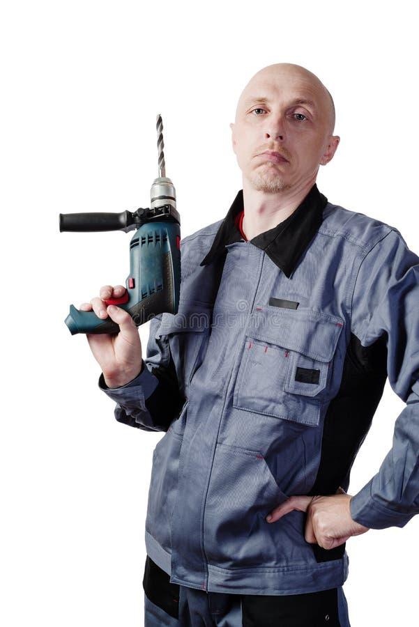 Mężczyzna w pracujących ubraniach z elektrycznym, musztruje wewnątrz jego ręki zdjęcia stock