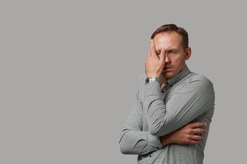 Mężczyzna w przypadkowej odzieży chuje jego twarz z jego rękami na szarym tle Emocjonalna, odważna twarz, Odizolowywaj?cy na biel zdjęcia royalty free