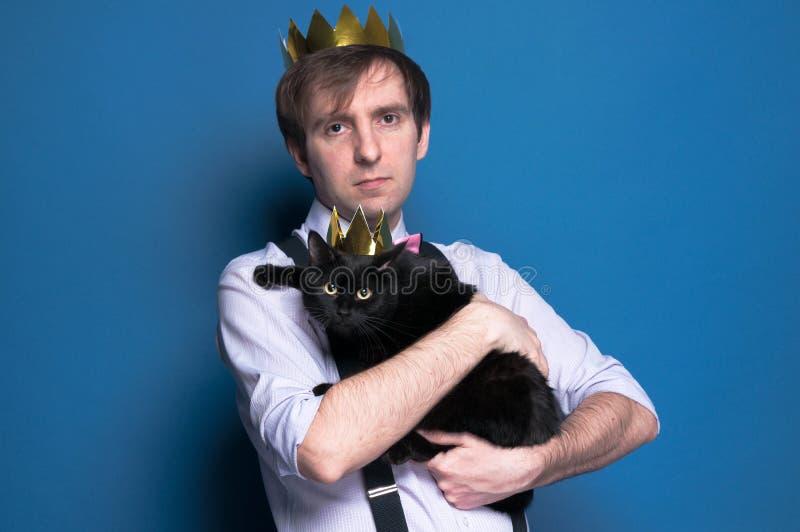 Mężczyzna w różowej koszula, suspender i domowej roboty złotej koronie, trzyma ślicznego czarnego kota w błyszczącej koronie zdjęcie stock