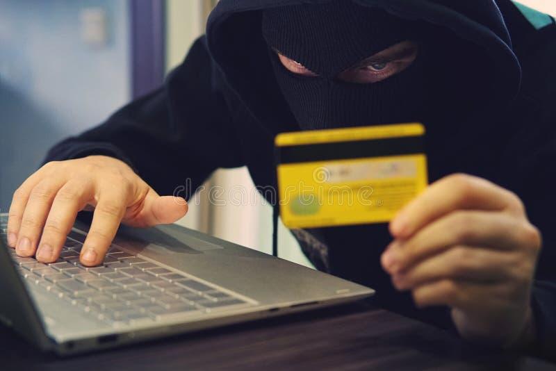 Mężczyzna w rabuś masce używa internet, konto bankowe i kredytowych udostępnienia, Phishing atak samiec z chowaną twarzą Hacker w zdjęcie stock