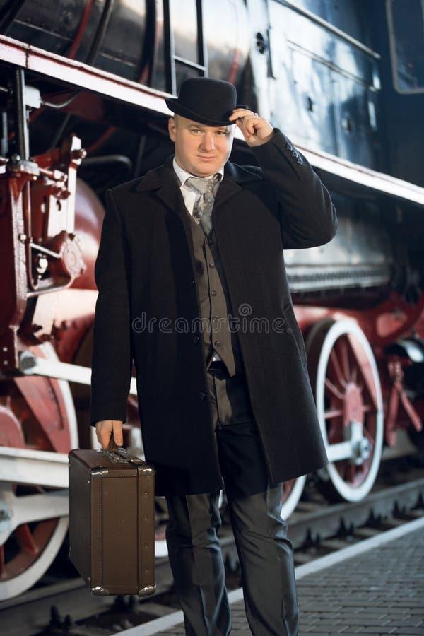 Mężczyzna w retro kostiumu, dęciaka kapeluszu i walizce pozuje przy starym locomot, obraz stock