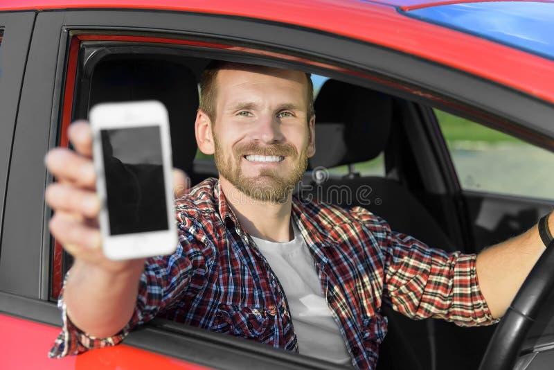 Mężczyzna w samochodowym jeżdżeniu pokazuje mądrze telefon zdjęcia royalty free