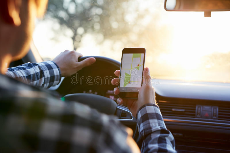 Mężczyzna w samochodowym mienie telefonie komórkowym z map gps nawigacją zdjęcie royalty free
