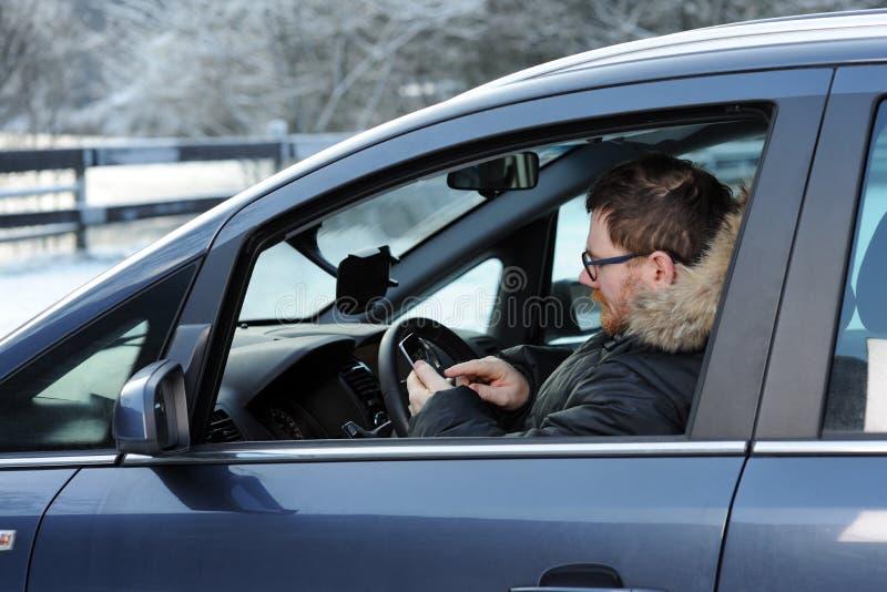 Mężczyzna w samochodzie z telefonem fotografia stock