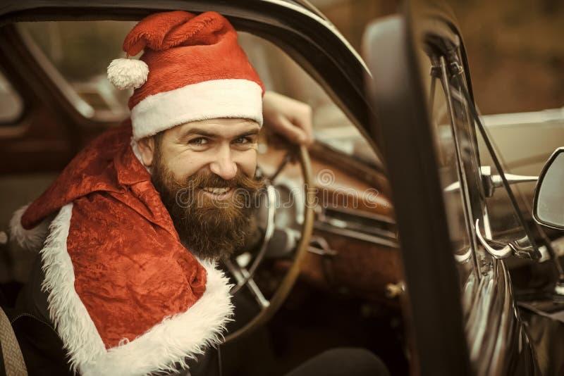 Mężczyzna w Santa kapeluszowym uśmiechu w retro samochodzie zdjęcia royalty free