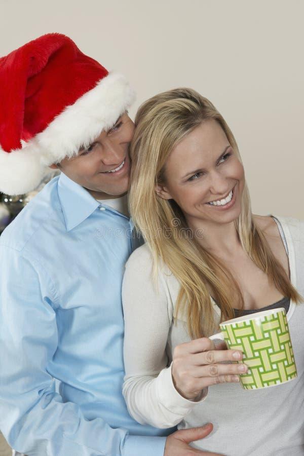 Mężczyzna W Santa obejmowania Kapeluszowej kobiecie Trzyma filiżankę obrazy stock