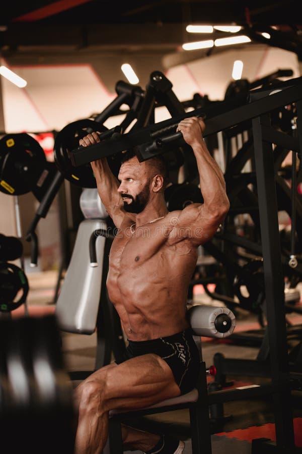 Mężczyzna w sporta temacie Sportowiec pracujący w gym out Mięśniowy bodybuilder robi ćwiczeniom fotografia stock