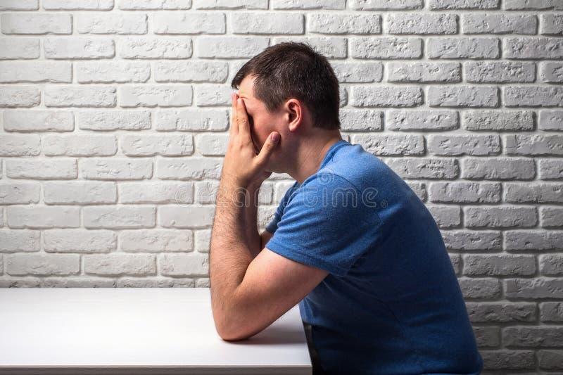 Mężczyzna w stresie trzyma jego głowę siedzi przy białym biurkiem z jego rękami obraz royalty free