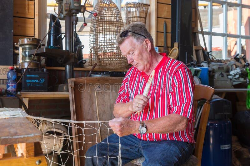 Mężczyzna w tradycyjnych Holenderskich kostiumowych zacerowanie sieciach rybackich w warsztacie zdjęcia stock