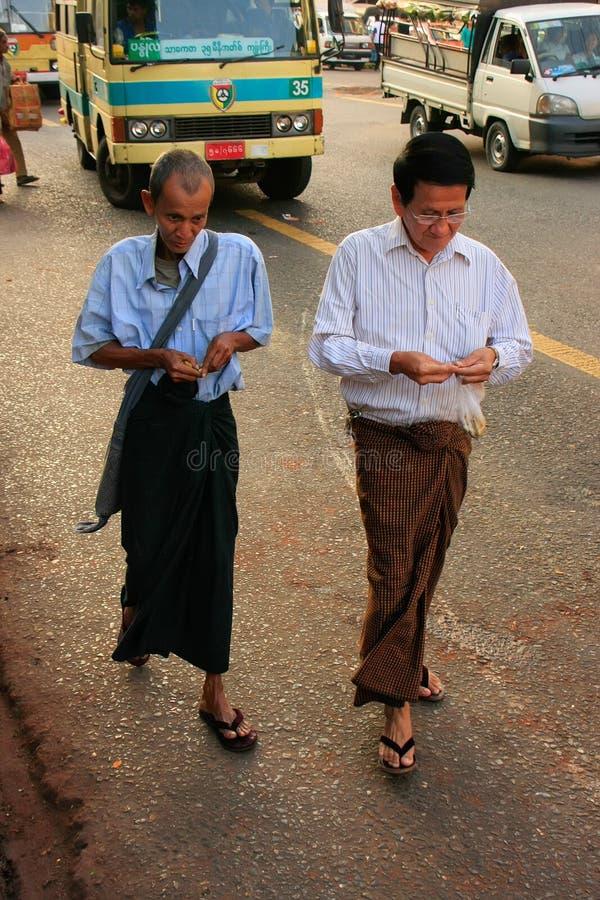 Mężczyzna w tradycyjnym smokingowym odprowadzeniu na ruchliwych ulicach Yangon, zdjęcia stock
