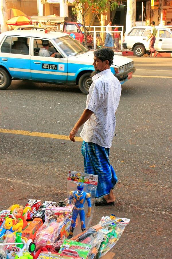 Mężczyzna w tradycyjnym smokingowym odprowadzeniu na ruchliwych ulicach Yangon, zdjęcie stock