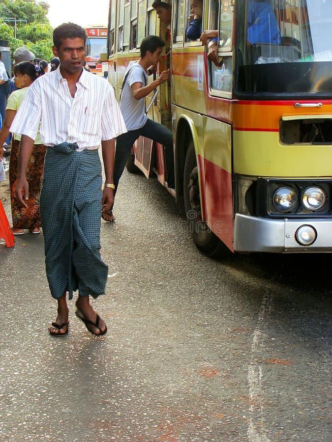 Mężczyzna w tradycyjnym smokingowym odprowadzeniu na ruchliwych ulicach Yangon, obraz stock