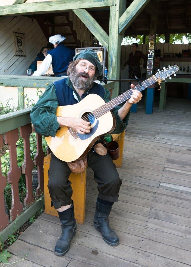 Mężczyzna w trubadurskim kostiumu bawić się gitarę przy Renesansowym festiwalem obrazy royalty free