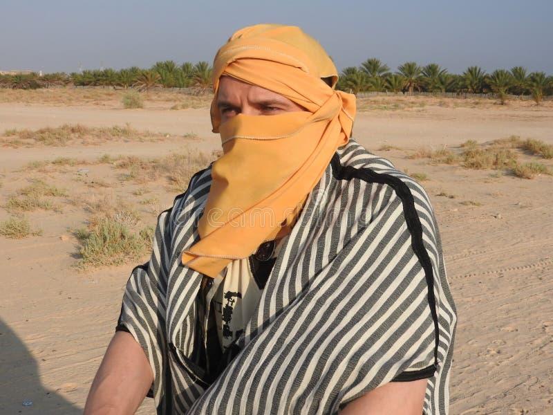 Mężczyzna w turbanie, twarz zakrywająca, z wielbłądem w saharze zdjęcie royalty free