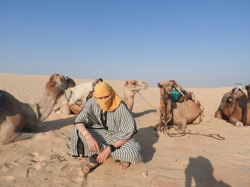 Mężczyzna w turbanie, twarz zakrywająca, z wielbłądem w saharze fotografia stock