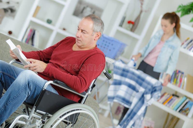 Mężczyzna w wózek inwalidzki czytelniczej książki opiekunu prasowaniu w tle zdjęcia royalty free