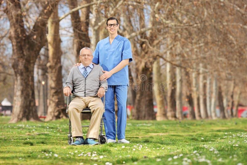 Mężczyzna w wózku inwalidzkim pozuje w parku męskiej pielęgniarce i zdjęcia royalty free