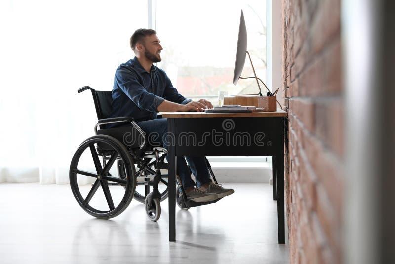 Mężczyzna w wózku inwalidzkim pracuje z komputerem przy stołem zdjęcie stock
