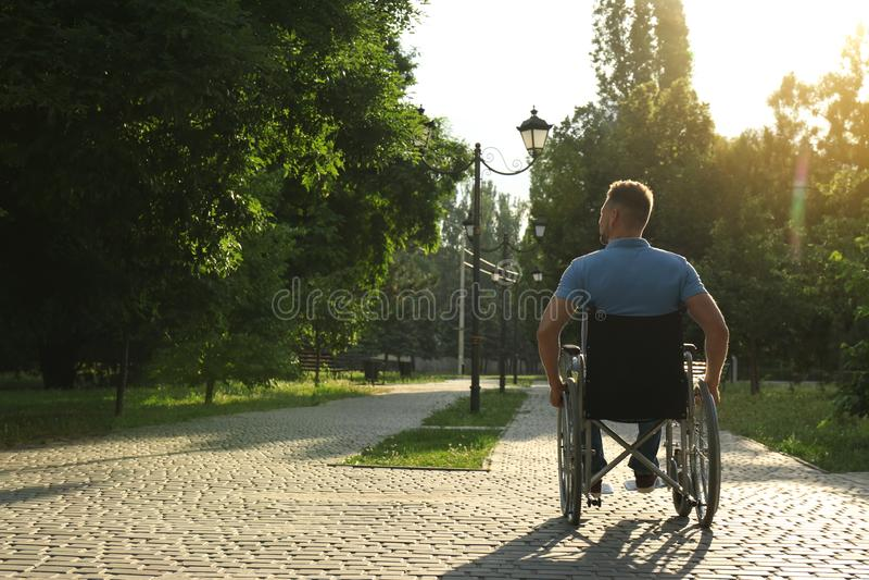 Mężczyzna w wózku inwalidzkim przy parkiem na słonecznym dniu kota komiczny myszy tekst zdjęcia royalty free