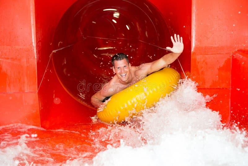 Mężczyzna w waterslide przy jawnym pływackim basenem zdjęcia royalty free