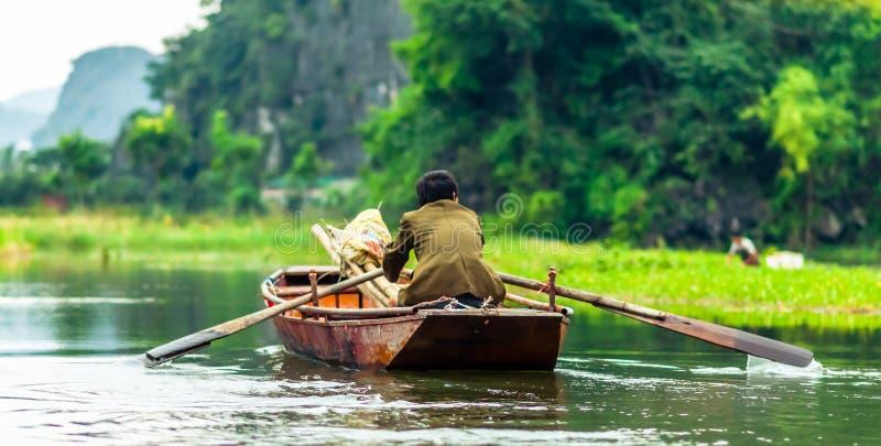Mężczyzna w wioślarskiej łodzi Nin Binh w Wietnam obraz royalty free