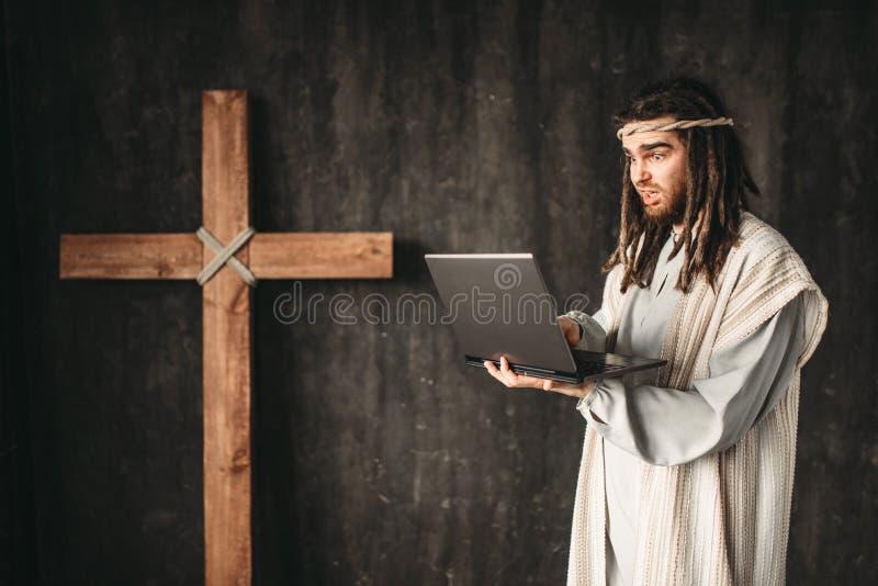 Mężczyzna w wizerunku jezus chrystus używa laptop fotografia royalty free