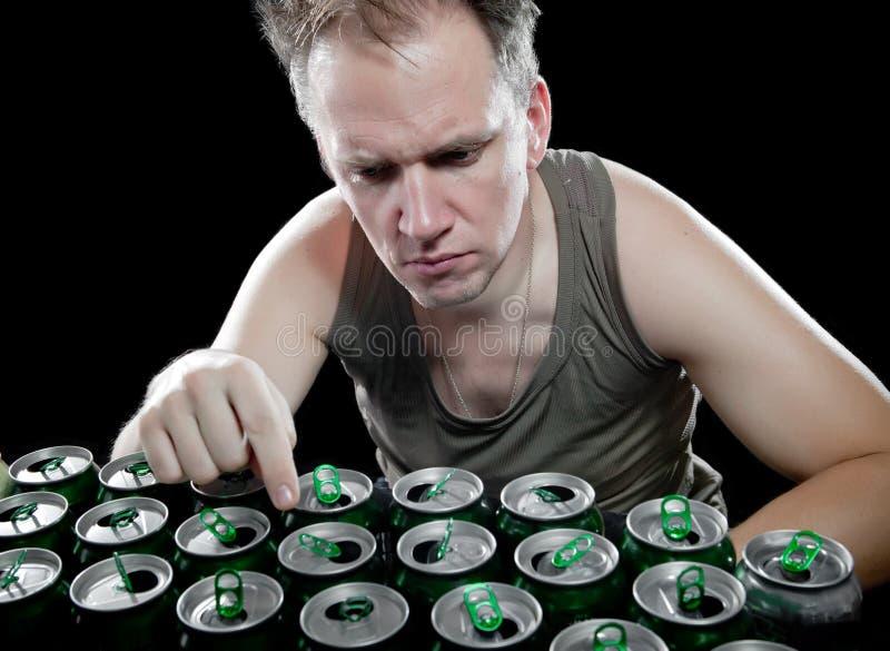 Mężczyzna w zielonym podkoszulku i liczbie puste piwne puszki na czarnym tle obrazy royalty free