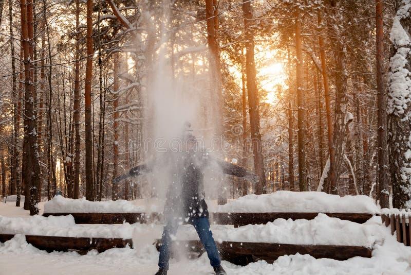 Mężczyzna w zimie w lesie bawić się z śniegiem i trząść daleko śnieg, stojaki pod drzewem, zakrywa je jak lawina, od obraz stock