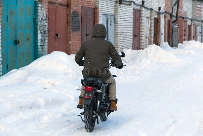 Mężczyzna w zimy odzieżowej jazdie motocykl obraz stock