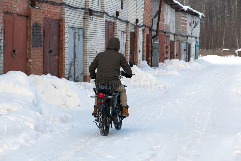 Mężczyzna w zimy odzieżowej jazdie motocykl na śnieżnej drodze zdjęcia royalty free