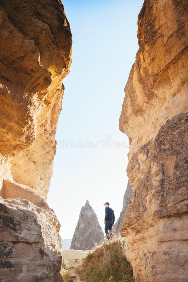 Mężczyzna w zmroku odzieżowym i baseball nakrętki stojakach między pięknymi skałami i podziwia krajobraz w Cappadocia wewnątrz obraz stock